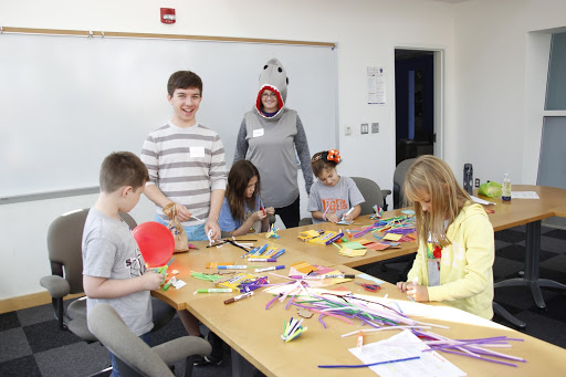 Two teachers, one dressed in a shark costume, supervise children making crafts.